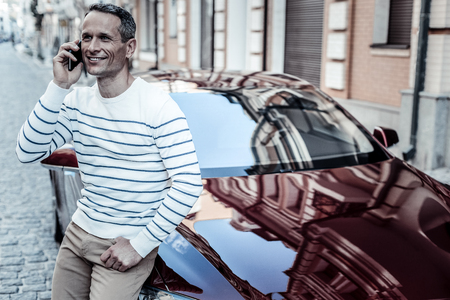 Great mood. Handsome nice delighted man standing near his car and talking on the phone while being in a good mood