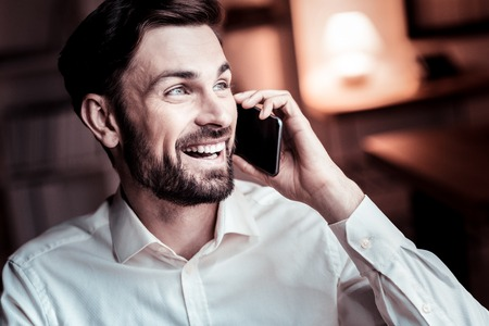 Happy pleasant stylish man spending time in the specious room smiling and having phone conversation.