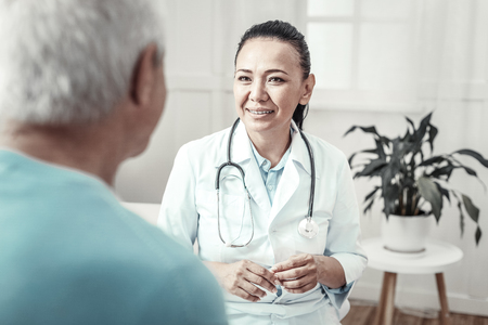 Best doctor. Skilled cute mature nurse sitting in the room near a man smiling and having consultation with him. Stock Photo