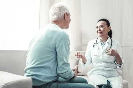 Family doctor. Pleasant joyful skilled doctor looking at the patient talking to him and gesticulating.