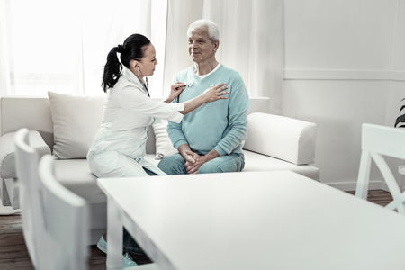 Breathe evenly. Grey haired modest aged man sitting in the room on the sofa near the table having medical examination doing nurses orders.