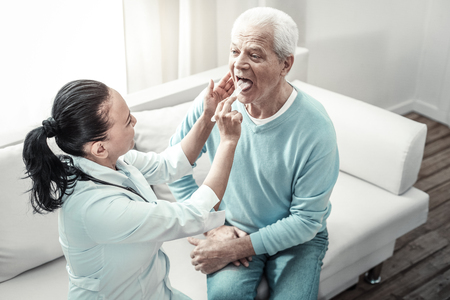 Let me help you. Old serious modest man holding his hands on his knees looking at the nurse and showing his tongue.
