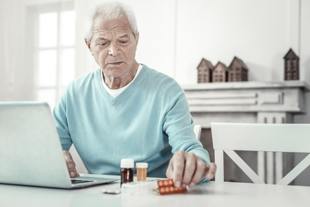 Serious illness. Deep aged sad man sitting in the room by the table using the laptop and overlooking pills. Stock Photo