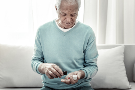 Doctors advice. Serious pleasant aged man sitting in the room on the sofa near the window pouring pills in hand and looking down.