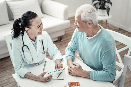 Weekly stock. Mature cute joyful nurse sitting by the table with her patient giving pills to him and smiling.