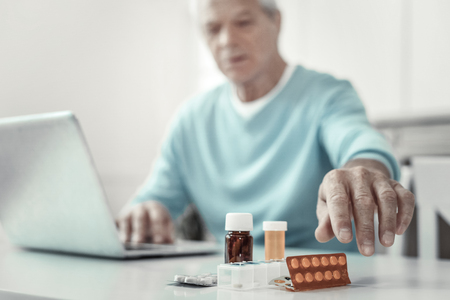 Its for me. Aged senior serious man sitting by the table holding hand near pills and trying to keep tablets. Stock Photo