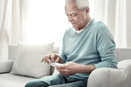 For healthy. Aged serious pleasant man sitting on the sofa taking a pill and looking at tablets.