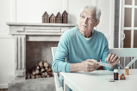 Thoughtful serious gray haired man sitting by the table in the bright room looking aside and keeping pills.