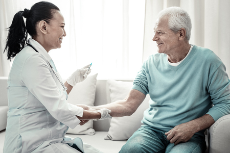Im not afraid. Joyful cute pleasant nurse sitting near her patient smiling and making injection for him. Stock Photo