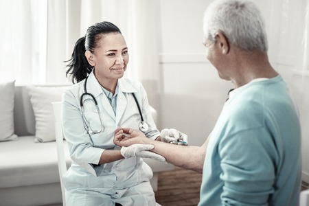 Joyful pleasant cute nurse sitting in the room with her patient smiling to him and making injection.