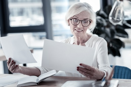 Let me check. Cheerful blonde keeping smile on her face and wrinkling forehead while checking documents
