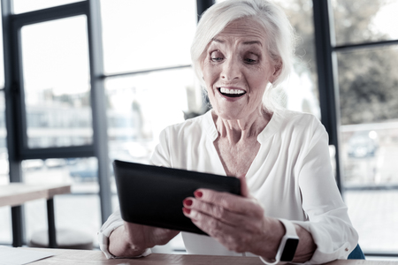 Express positivity. Cheerful female person keeping smile on her face and holding tablet in both hands while looking at it Stock Photo