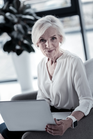 Self-confidence. Attractive senior woman expressing positivity and holding laptop while being in the office