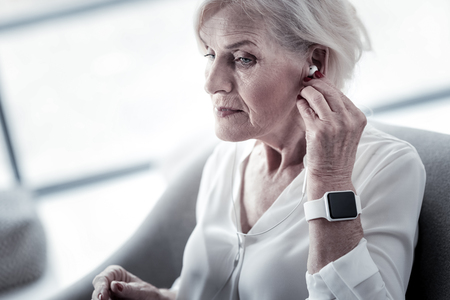 Serious blonde mature woman raising eyebrow and touching her gadget while looking forward