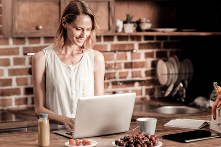Remote work. Attractive cheerful pleasant woman smiling and looking at the laptop screen while working remotely Stock Photo