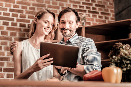 Happy together. Delighted nice pleasant couple standing together and smiling while looking at the tablet screen