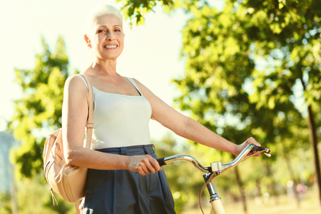 Outdoor activity. Positive nice elderly woman holding her bike and smiling while looking at you Stock Photo