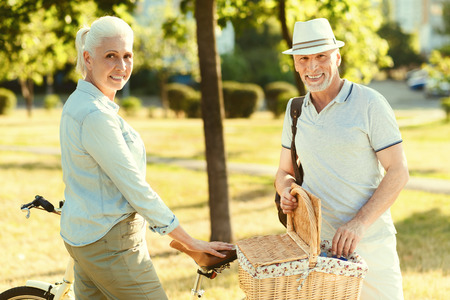 Pleasant picnic. Delighted nice elderly couple smiling and being in a positive mood while going on a picnic together Stock Photo