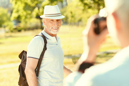 Happy moments. Cheerful delighted nice man smiling and looking into the camera while posing for a photo Stock Photo