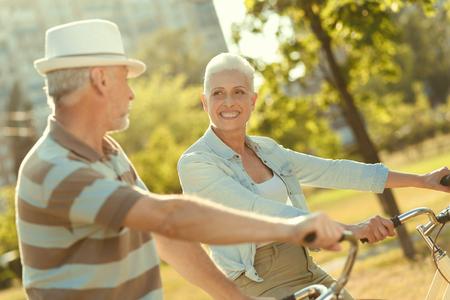 彼女のケアを示しながら、彼女の夫を抱きしめ、笑顔で見栄えの良い年配の女性を喜ばせました