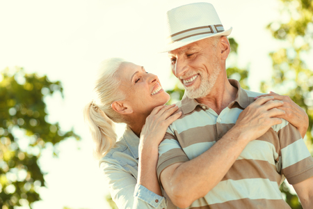 Happy together. Joyful nice positive woman standing behind her husband and looking at him while feeling happy