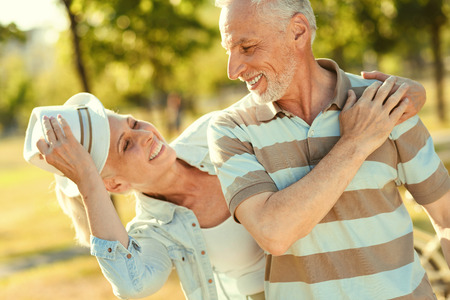 Wonderful mood. Delighted nice aged couple looking at each other and smiling while enjoying their time together