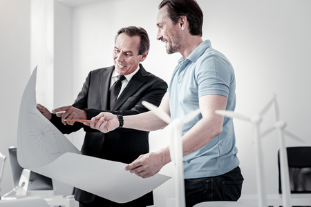 Show in to me. Positive delighted young man standing in semi position and holding big sketch while discussing with his boss