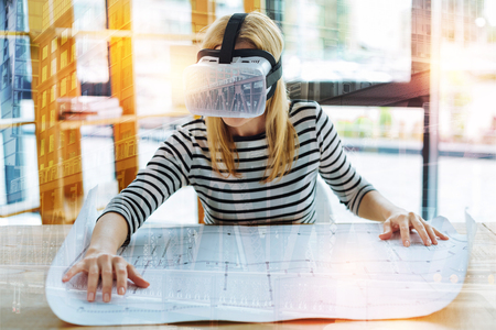 Clever experienced progressive engineer sitting at the table and working with a detailed scheme while wearing convenient virtual reality glasses