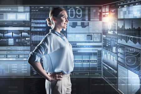Well done. Cheerful smart young programmer looking satisfied with her amazing work while standing with her hands on the hips and smiling Stock Photo