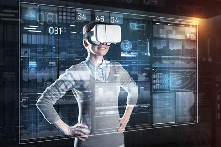 New vision. Clever calm cheerful woman smiling and feeling confident while wearing modern convenient virtual reality glasses and working at the new program in her office