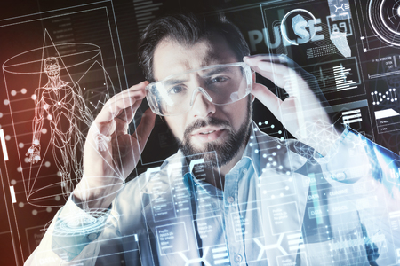 Convenient glasses. Calm serious smart doctor wearing protecting glasses and feeling interested while standing in front of a transparent screen on his futuristic laboratory