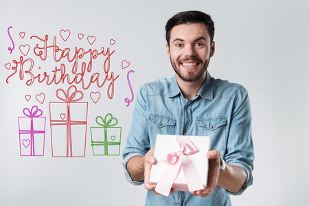 Happy Birthday. Cheerful friendly attentive man feeling happy and smiling while being at the birthday party with a beautiful present in his hands Stock Photo