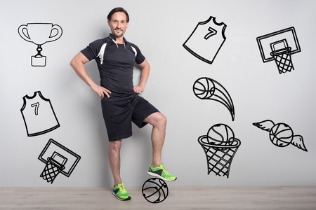 Confident sportsman. Experienced skilled handsome basketball player feeling confident while standing with his foot on a ball and smiling happily Banco de Imagens