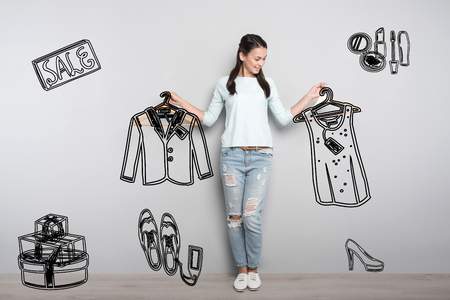 Amazing sale. Beautiful young woman seeing a big sale and using this opportunity for buying new clothes with a discount
