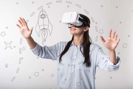 Virtual reality. Young progressive woman feeling impressed and smiling while wearing modern convenient virtual reality glasses and exploring the space with a help of them Stok Fotoğraf - 97283618