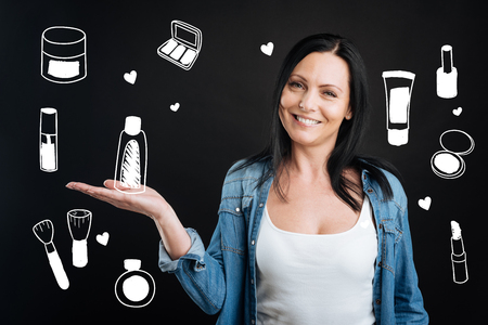 Favorite cosmetics. Kind pleasant beautiful woman being in a good mood and smiling cheerfully while standing against the grey background and showing her new amazing cosmetics