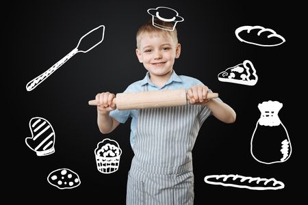 Little chef. Cheerful little smiling boy holding a wooden rolling pin in his hands while pretending to be a real professional cook