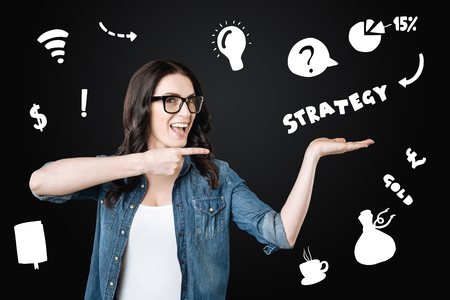 Perfect strategy. Clever qualified optimistic employee feeling excited while smiling and showing her new strategy Imagens - 97283739