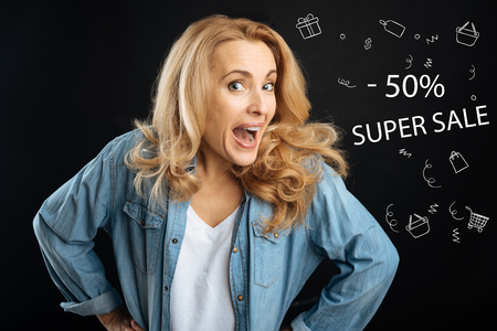 Super sale. Emotional enthusiastic housewife feeling excited while discovering the information about discount prices and smiling while going shopping
