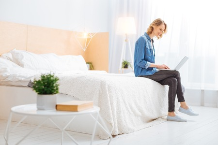 Reading news. Calm smiling young woman sitting on her comfortable soft bed and looking at the screen of a modern convenient laptop while reading the latest news in the Internet Zdjęcie Seryjne