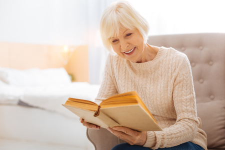 Exciting book. Pleasant cute cheerful pensioner spending a good time alone while sitting in a comfortable cozy armchair and reading an interesting book Foto de archivo