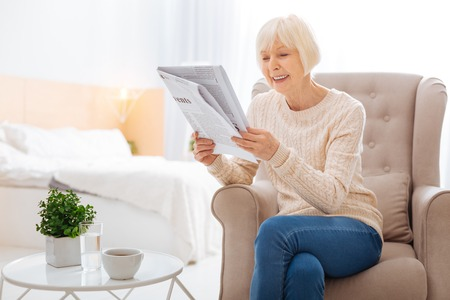 Interesting article. Cheerful positive aged woman feeling happy while sitting in a cozy soft armchair with a cup of tasty tea by her side and reading an exciting article in a local newspaper