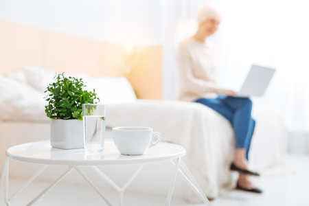 Laconic. Pleasant calm aged woman feeling interested while sitting on a soft bed with her modern laptop while having all the necessary items on a little convenient white table next to her