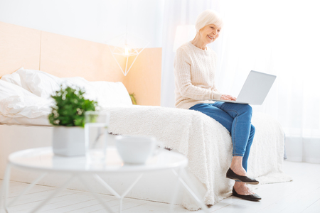 Relaxing pensioner. Cute positive emotional senior woman feeling happy and relaxed while sitting on a soft comfortable big bed and looking at the screen of a wonderful modern laptop