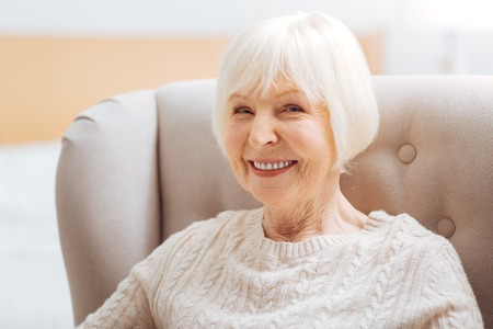 Pretty pensioner. Cute pretty senior woman feeling happy while sitting in a comfortable soft armchair and waiting for her kind young granddaughter to come and visit her