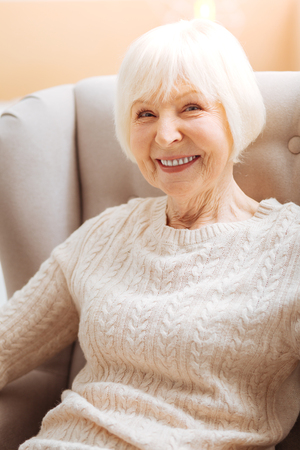 Baby boomer. Cute pretty senior woman smiling and feeling happy while sitting in a soft comfortable armchair and waiting for her nice kind relatives