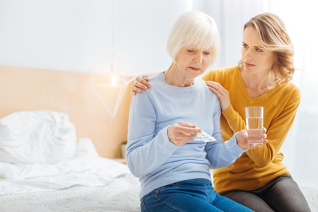 Unpleasant condition. Tired senior woman feeling bad while sitting in the light comfortable bedroom with her kind loving attentive granddaughter showing her support Stock Photo