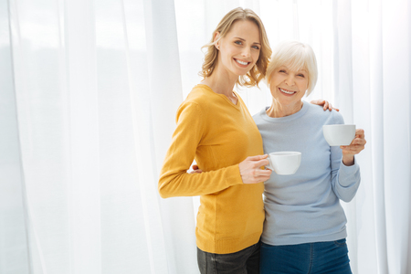 Happy people. Emotional delighted elderly woman feeling happy while standing with a cup of tea and hugging her positive kind attentive granddaughter