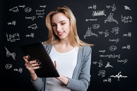 Clever mathematician. Beautiful young cheerful mathematician looking calm and pleased while standing with a modern useful tablet in her hands and working with a help of this convenient device Banco de Imagens - 97288232
