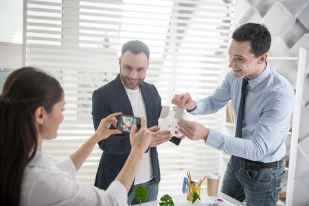 Say cheese. Good-looking content young dark-haired architects smiling and holding a house miniature while their colleague taking photos of them Stock Photo